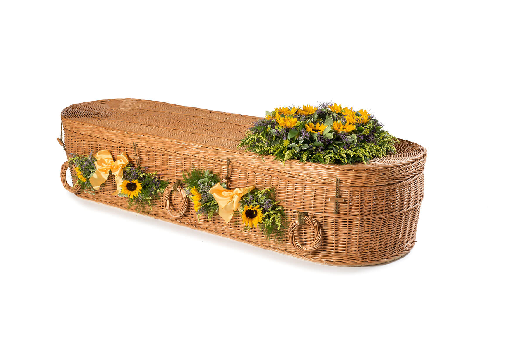 Wicker rounded coffin with flowers on