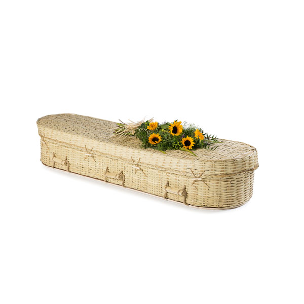 White Wicker rounded coffin with flowers on