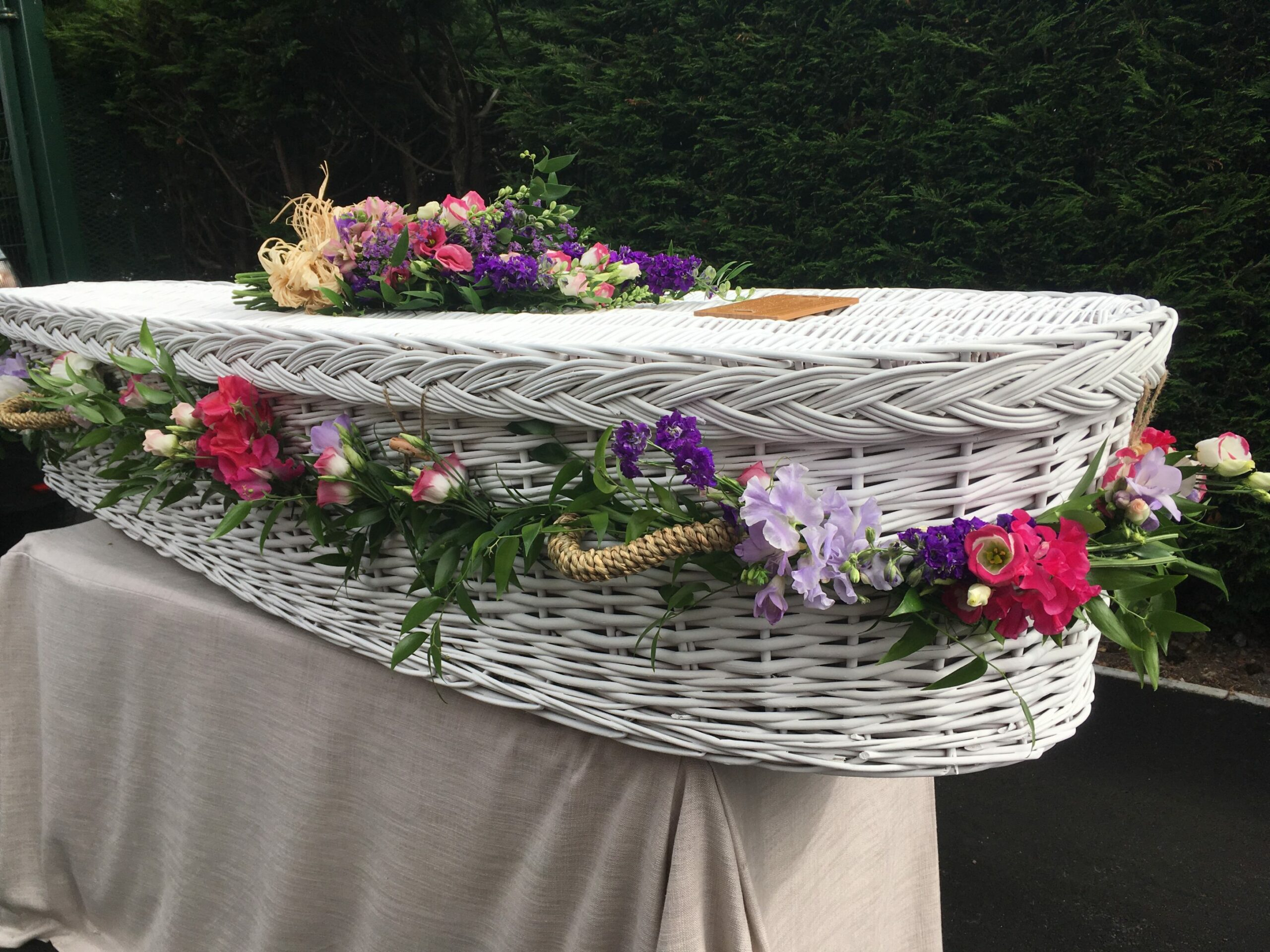 White wicker coffin with flowers