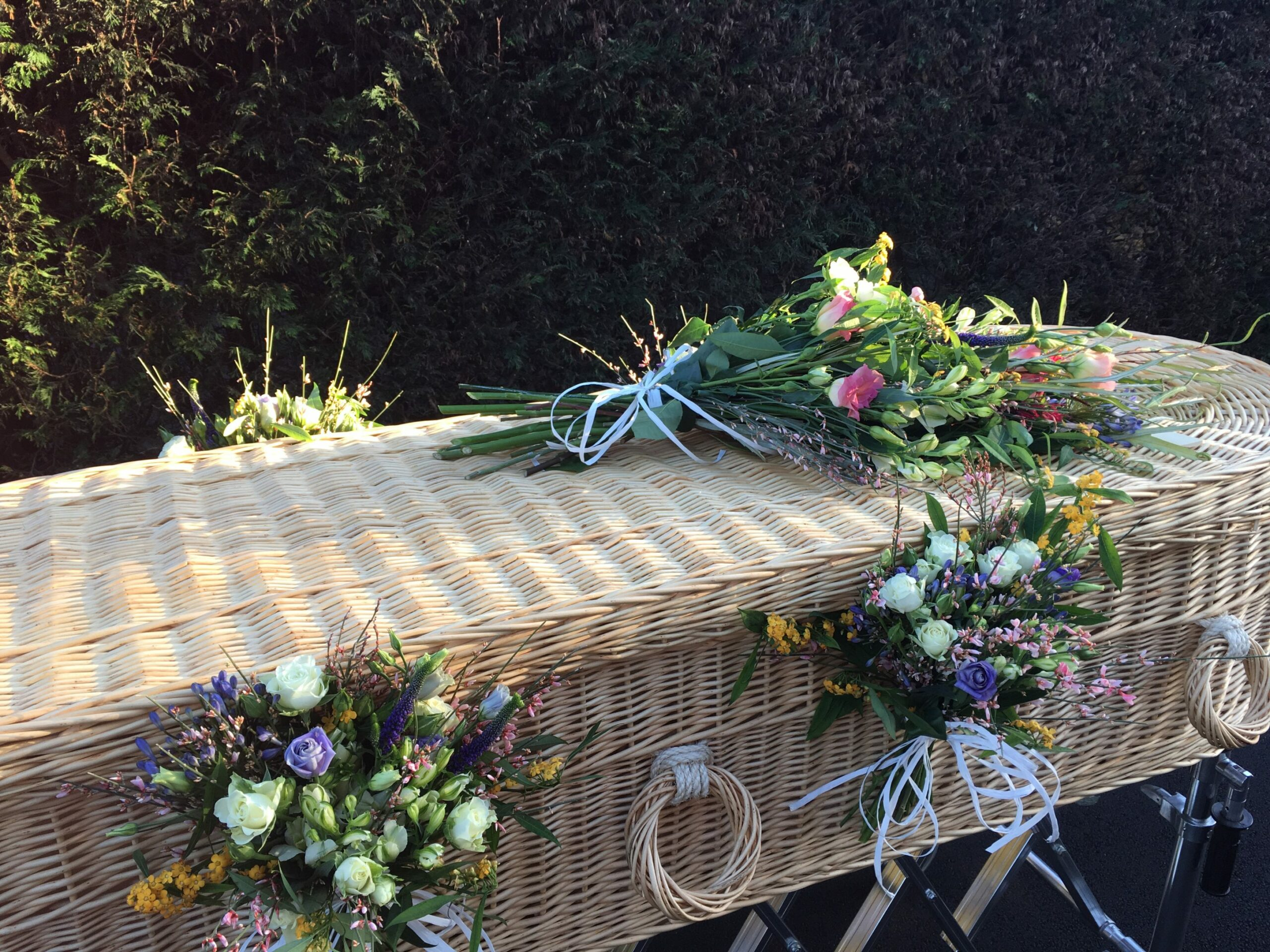Wicker coffin with flowers on