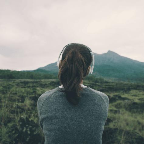 Woman in headphones looking at hills