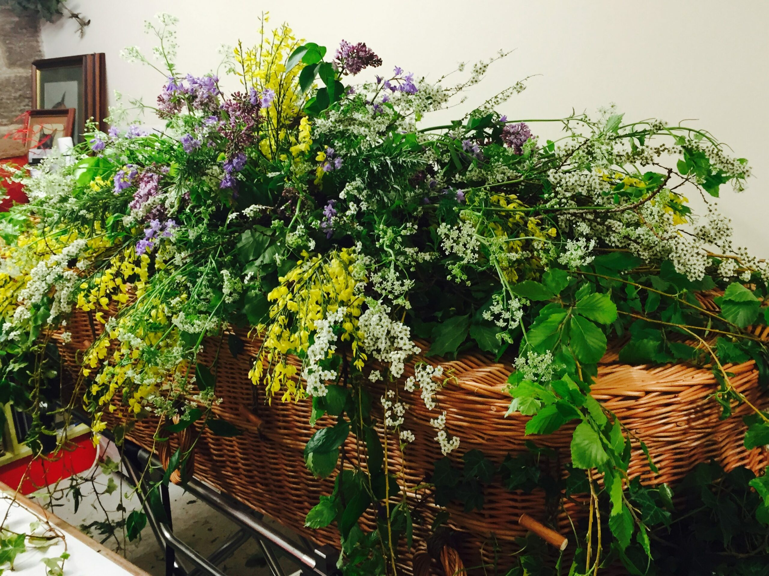 Wicker coffin with lots of flowers on